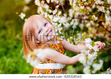 cute little girl near blooming apple trees and cherry - stock photo