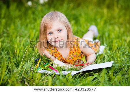 cute little girl near blooming apple trees and cherry drawing pencils
