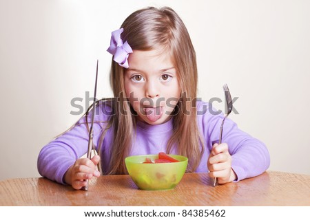Cute little girl not wanting to eat healthy food - stock photo