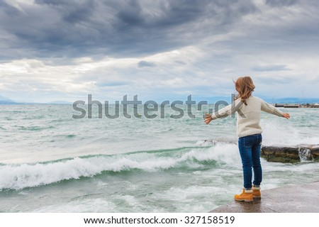 Cute little girl of 8 years old playing by the lake on a very windy day, wearing warm white knitted pullover, arms wide open, back view - stock photo