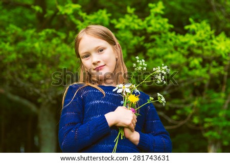 Cute little girl of 7 years old playing in a forest, picking wildflowers - stock photo
