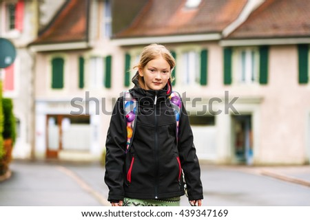 Cute little girl of 8 years old wearing backpack, walking to school - stock photo
