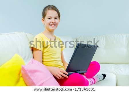cute little girl on a sofa with a laptop - stock photo