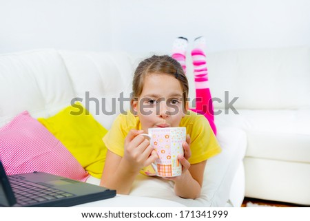 cute little girl on a sofa with a laptop and cup of tea - stock photo