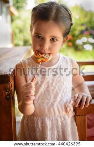 Cute little girl on backyard holding in hand big multicolor spiral lollipop candy, small child wearing pink dress outdoors in summer eating sweet sugar candy, dental health and care concept - stock photo