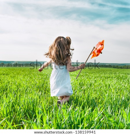 cute little girl on grass in summer day holds windmill in hand - stock photo