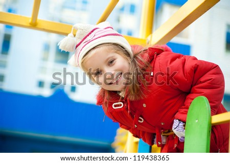 Cute little girl on outdoor playground looking at camera - stock photo