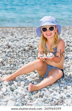 Cute little girl on the beach holds in the hands stones with images of smiles