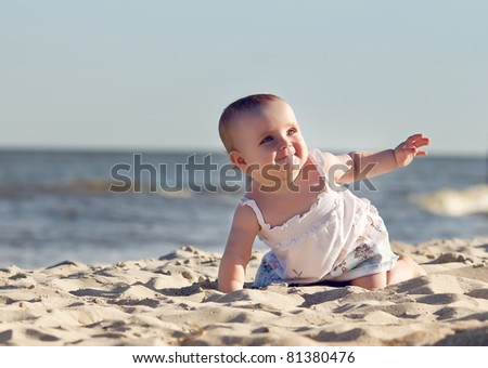 Cute little girl on the beach in summer day - stock photo