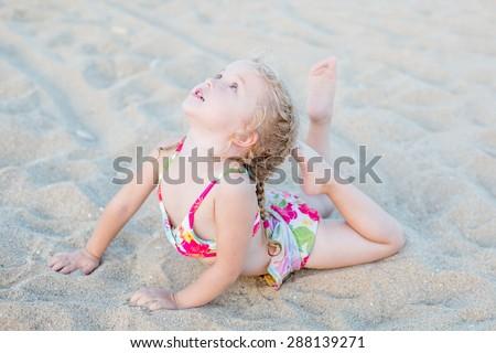 cute little girl on the beach stretch - stock photo