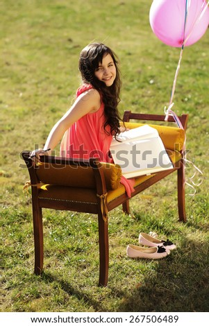 Cute little girl on the bench holding a sketch-book, vertical picture - stock photo