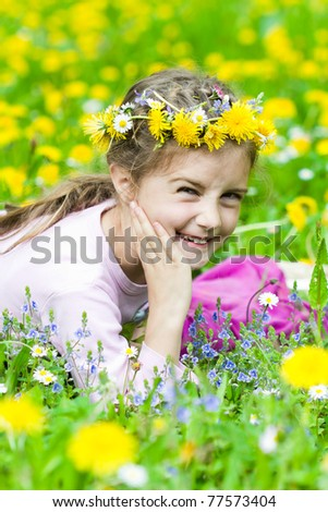 Cute little girl on the dandelion meadow in spring day - stock photo