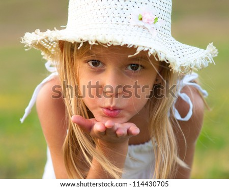 Cute little girl on the meadow blowing a kiss toward you on beautiful summer day. - stock photo