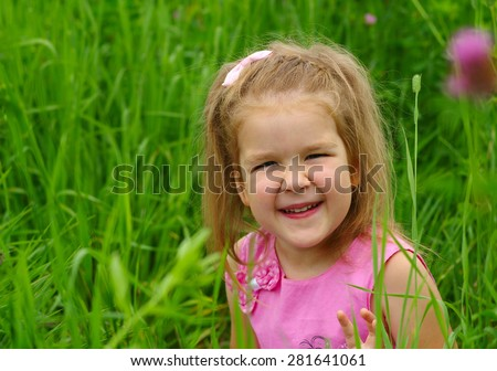 Cute little girl on the meadow in spring day.  - stock photo