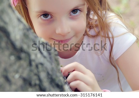 Cute little girl on the meadow in spring day- happy girl - stock photo