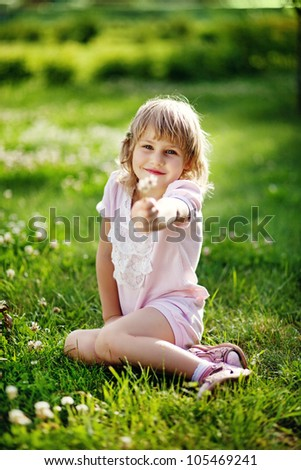 Cute little girl on the meadow in summer day - stock photo