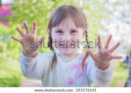 Cute little girl on the meadow in summer day. - stock photo