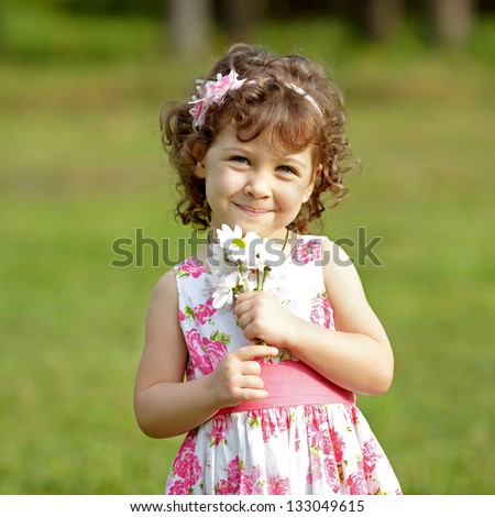 Cute little girl on the meadow in summer day with flowers