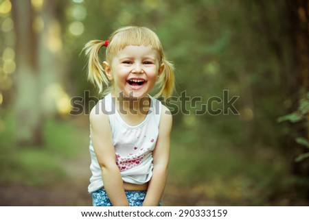 Cute little girl on the meadow laughs in summer day