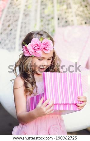 Cute little girl open her birthday gift box - stock photo