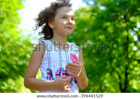Cute little girl outdoors with curly hair in the wind. Smiling, happy toddler child, kid on a windy day breathing fresh air in the green park on the nature at summer or spring. - stock photo