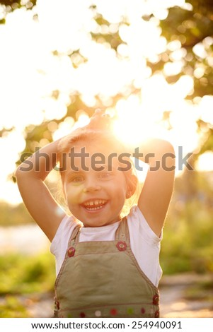 Cute little girl outside smiling happily with early morning sunlight filtering through the trees - stock photo