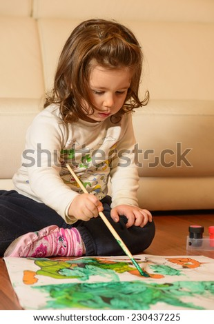Cute little girl painting at home. Beautiful child having fun at home painting on coloring book on the floor - stock photo