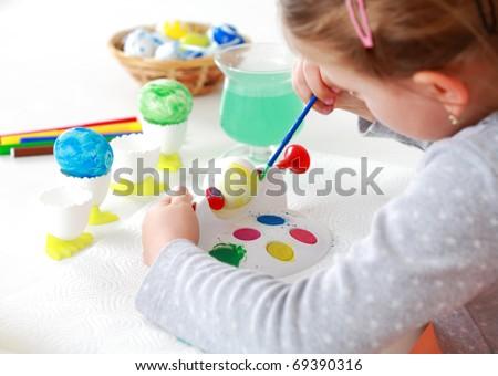 Cute little girl painting Easter eggs - stock photo