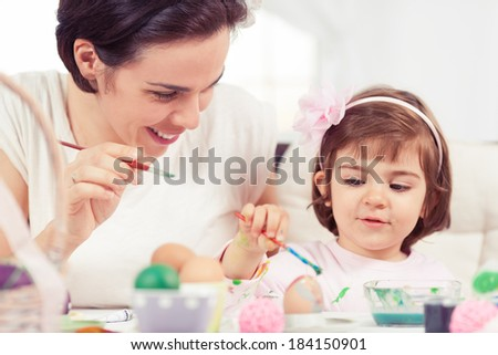 Cute little girl painting Easter eggs with mommy. - stock photo