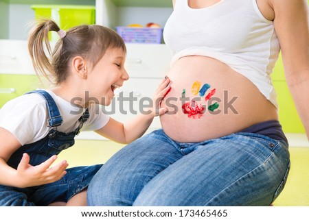 Cute little girl painting on pregnant mothers belly