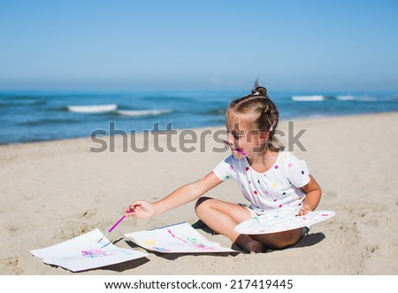 cute little girl painting on the seaside - stock photo