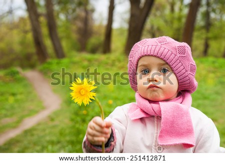 cute little girl picking flowers in the meadow in spring day outdoors, - stock photo