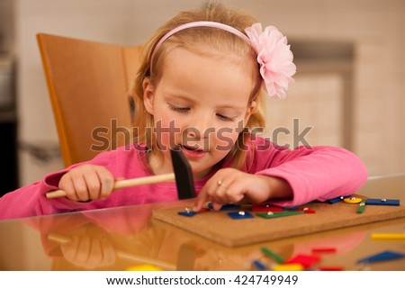 Cute little girl pin pointing blocks into wooden board playing with her toys - stock photo