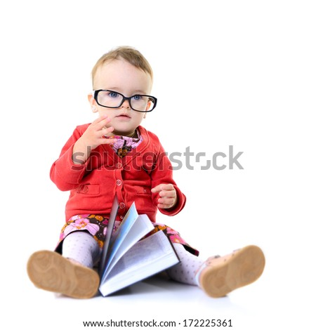 Cute little girl play with book and glasses, isolated over white - stock photo