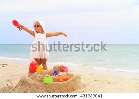 cute little girl play with sand on beach - stock photo