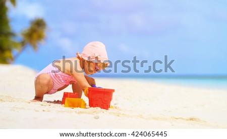 cute little girl play with sand on the beach - stock photo