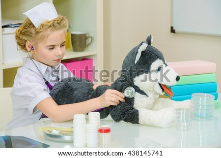 Cute little girl playing a doctor at home. Different occupations. Children's Health, Pediatrics. - stock photo