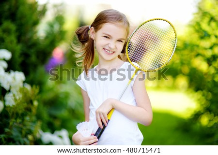 Cute little girl playing badminton outdoors on warm and sunny summer day
