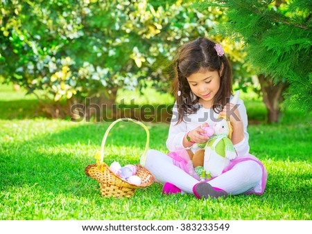 Cute little girl playing Easter game, find colorful eggs and fed them a bunny toy, having fun in fresh green garden, happy spring religious holiday - stock photo