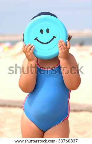 cute little girl playing frisbee on the beach with a big smile