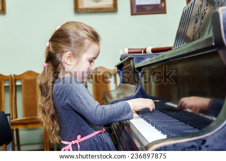 Cute little girl playing grand piano in music school - stock photo
