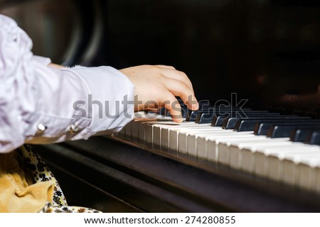 Cute little girl playing grand piano in music school, childhood concept - stock photo