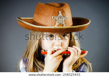 Cute little girl playing harmonica, music concept - stock photo