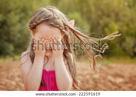 Cute little girl playing hide and seek with camera - stock photo