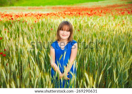 Cute little girl playing in a wheat field on a summer day - stock photo