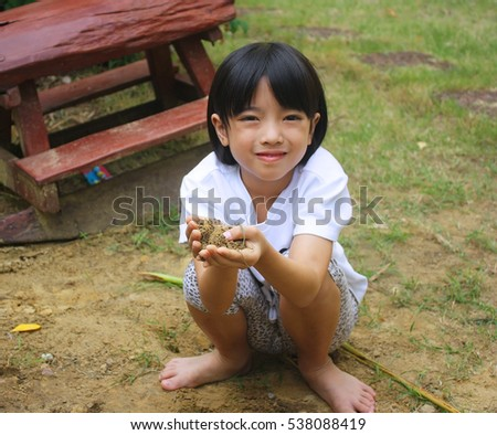 Cute little girl playing in garden with dirty hands