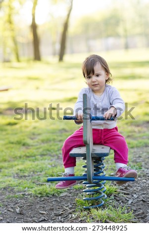 Cute little girl playing in the park on spring day - stock photo