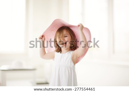 Cute little girl playing indoors with large pink summer hat. - stock photo