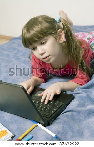 Cute little girl playing on laptop