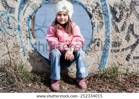 Cute little girl playing on outdoor playground equipment  - stock photo
